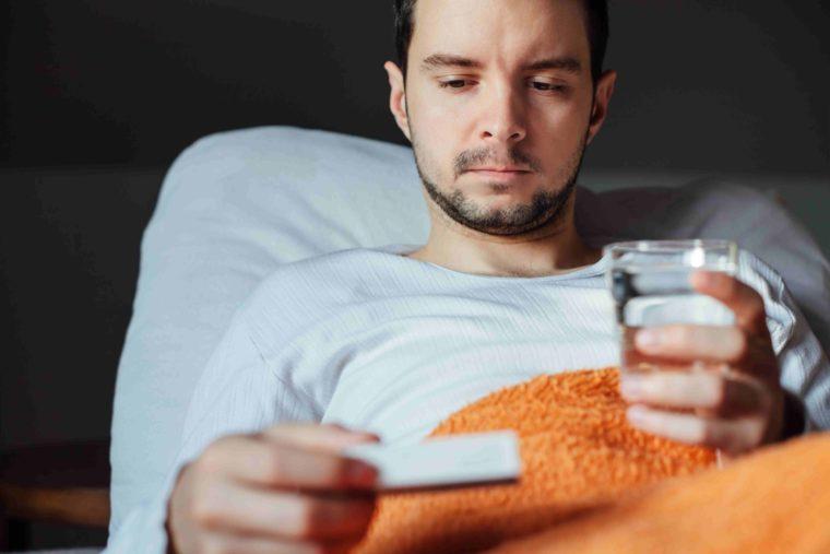 Больной мужчина пьёт таблетки